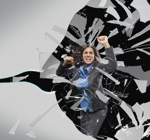 Stock Photo: 1589R-73760 Hispanic businesswoman breaking through glass barrier