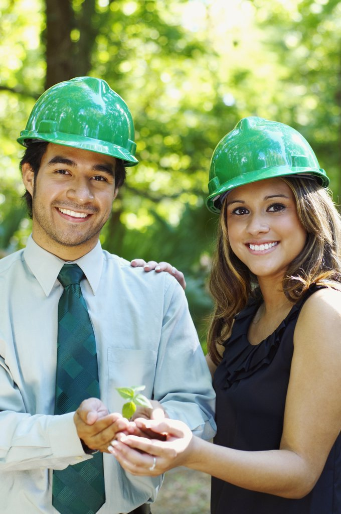 Hispanic business people with green hard hats holding tree sprout : Stock Photo