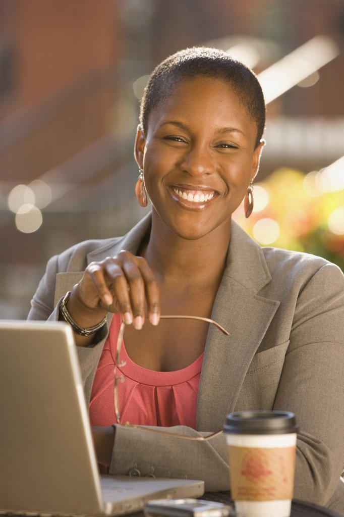 Smiling African businesswoman working outdoors : Stock Photo