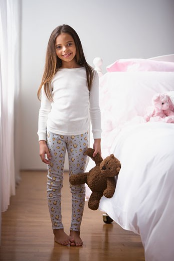 Stock Photo: 1589R-74474 Hispanic girl in pajamas holding teddy bear