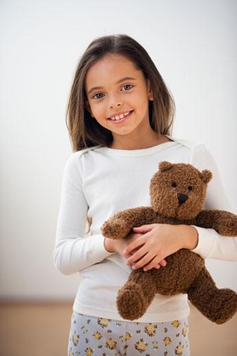 Hispanic girl in pajamas holding teddy bear : Stock Photo