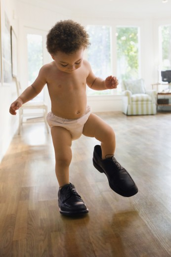 Mixed race boy wearing father's shoes : Stock Photo