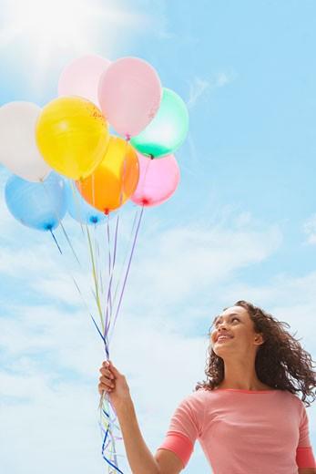 Stock Photo: 1589R-74513 Mixed race teenage girl holding bunch of balloons