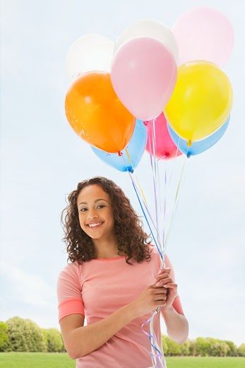 Mixed race teenage girl holding bunch of balloons : Stock Photo