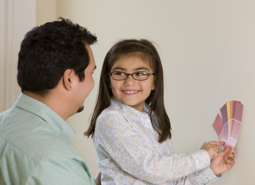 Hispanic girl with father choosing paint colors : Stock Photo