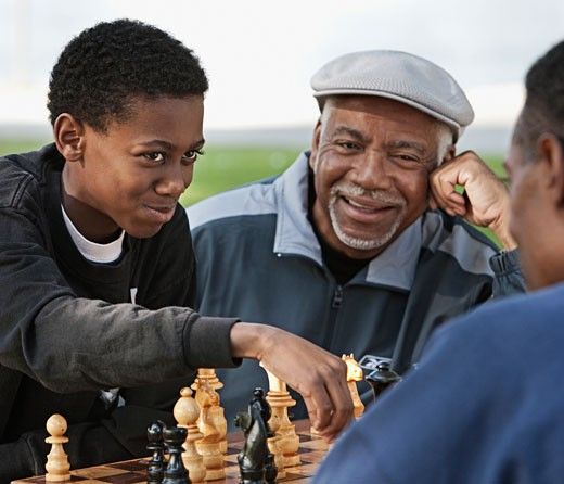 African boy playing chess against father outdoors : Stock Photo