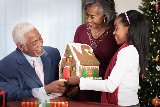 African man being surprised with gingerbread house : Stock Photo