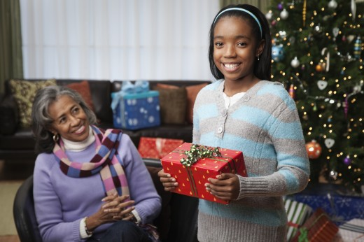 African girl giving grandmother Christmas gift : Stock Photo