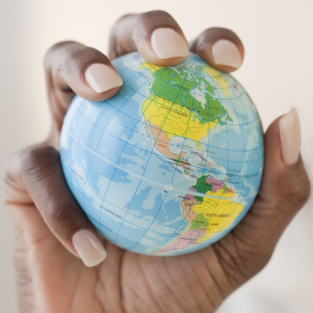 African woman holding globe in hand : Stock Photo