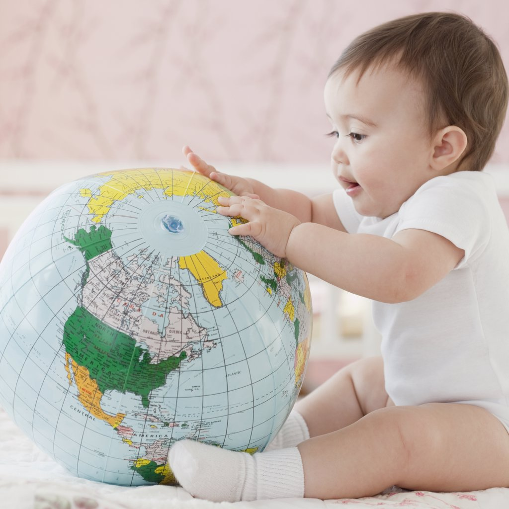 Stock Photo: 1589R-74985 Mixed race baby girl looking at blow-up globe