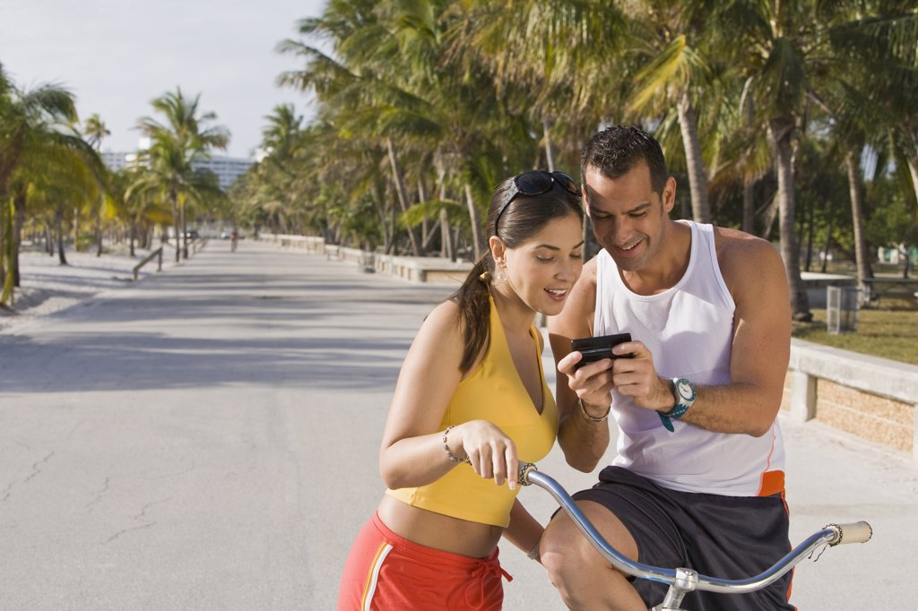 Stock Photo: 1589R-75027 Hispanic couple on bicycles looking at cell phone