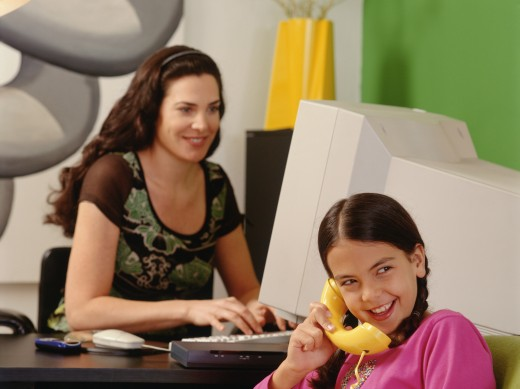 Daughter talking on telephone while mother works in background : Stock Photo