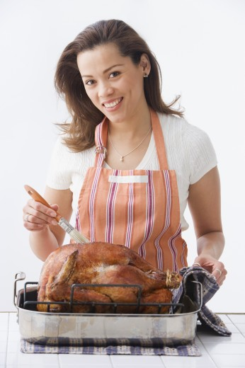 Stock Photo: 1589R-75142 Hispanic woman basting turkey