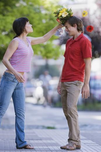 Stock Photo: 1589R-75235 Hispanic woman hitting boyfriend with bouquet of flowers