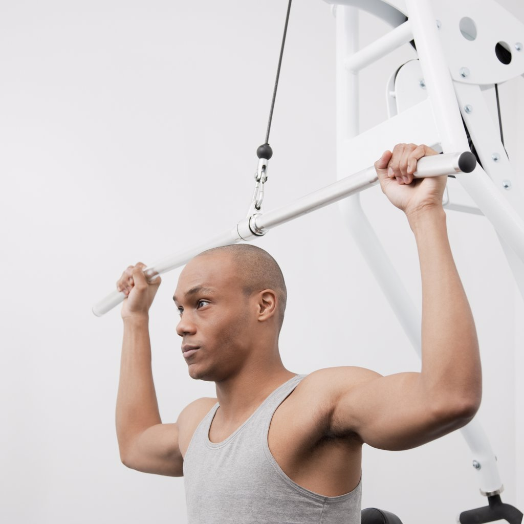 African man using weight machine in health club : Stock Photo