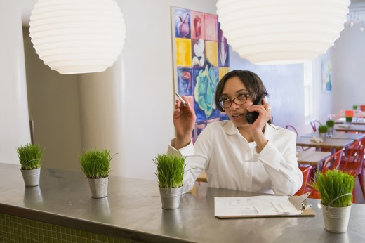Mixed race woman talking on telephone in cafe : Stock Photo
