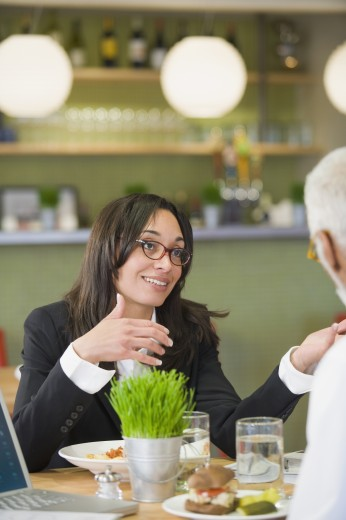 Mixed race businesswoman having lunch with co-worker : Stock Photo