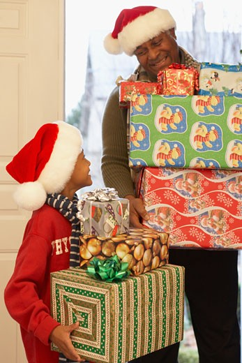 Stock Photo: 1589R-75479 African grandfather and grandson carrying Christmas gifts