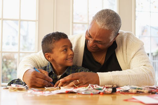 African grandfather helping grandson with project : Stock Photo