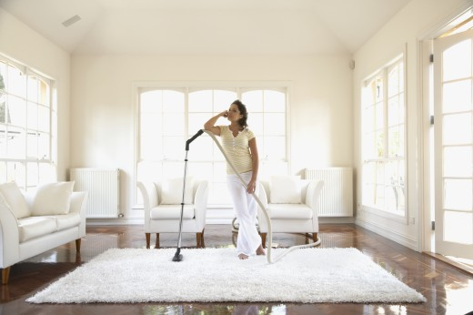 Hispanic woman vacuuming floor : Stock Photo