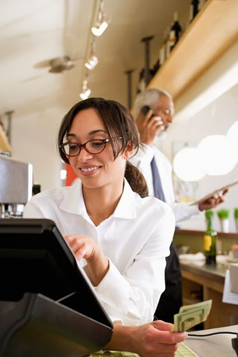Mixed race cashier ringing up sale in cafe : Stock Photo