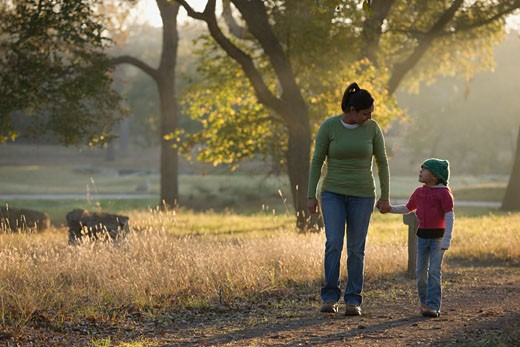 Hispanic mother walking with daughter in park : Stock Photo