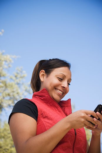 Stock Photo: 1589R-76112 Hispanic woman text messaging on cell phones