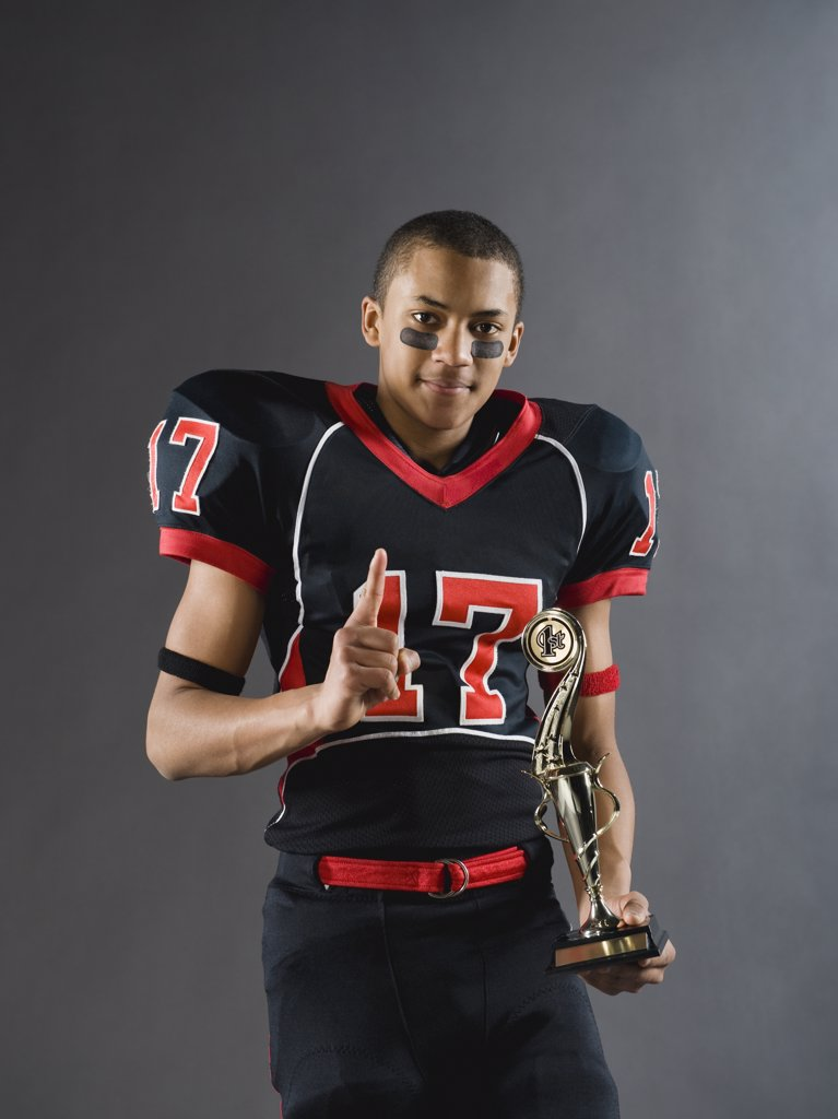 Mixed race football player holding trophy and gesturing : Stock Photo