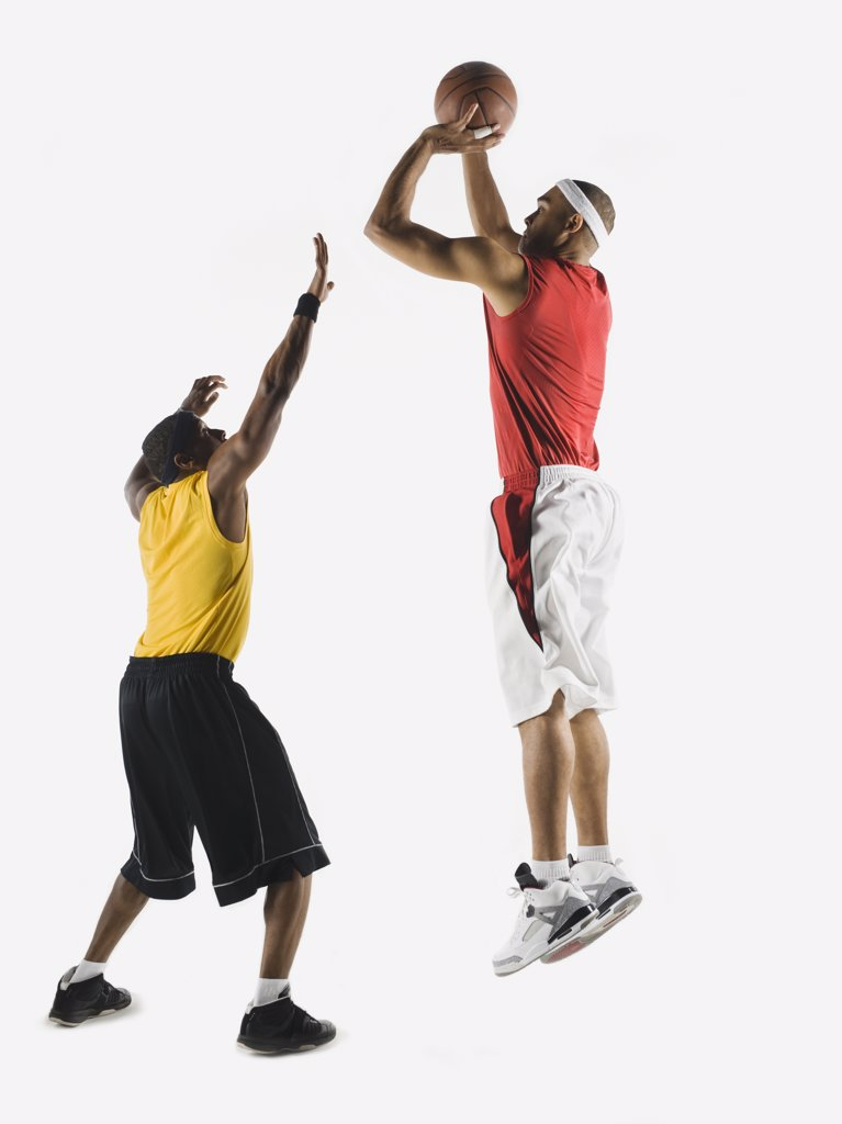 African man shooting basketball over opponent : Stock Photo