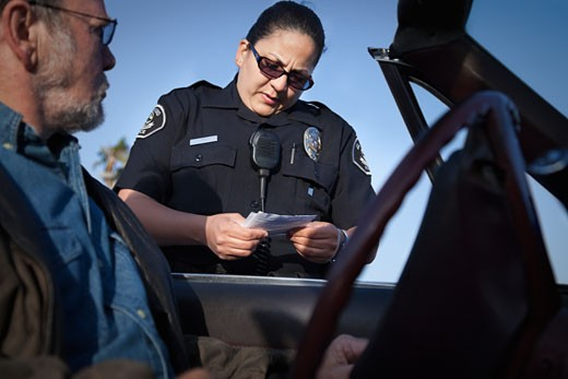 Policewoman checking paperwork of man in convertible : Stock Photo