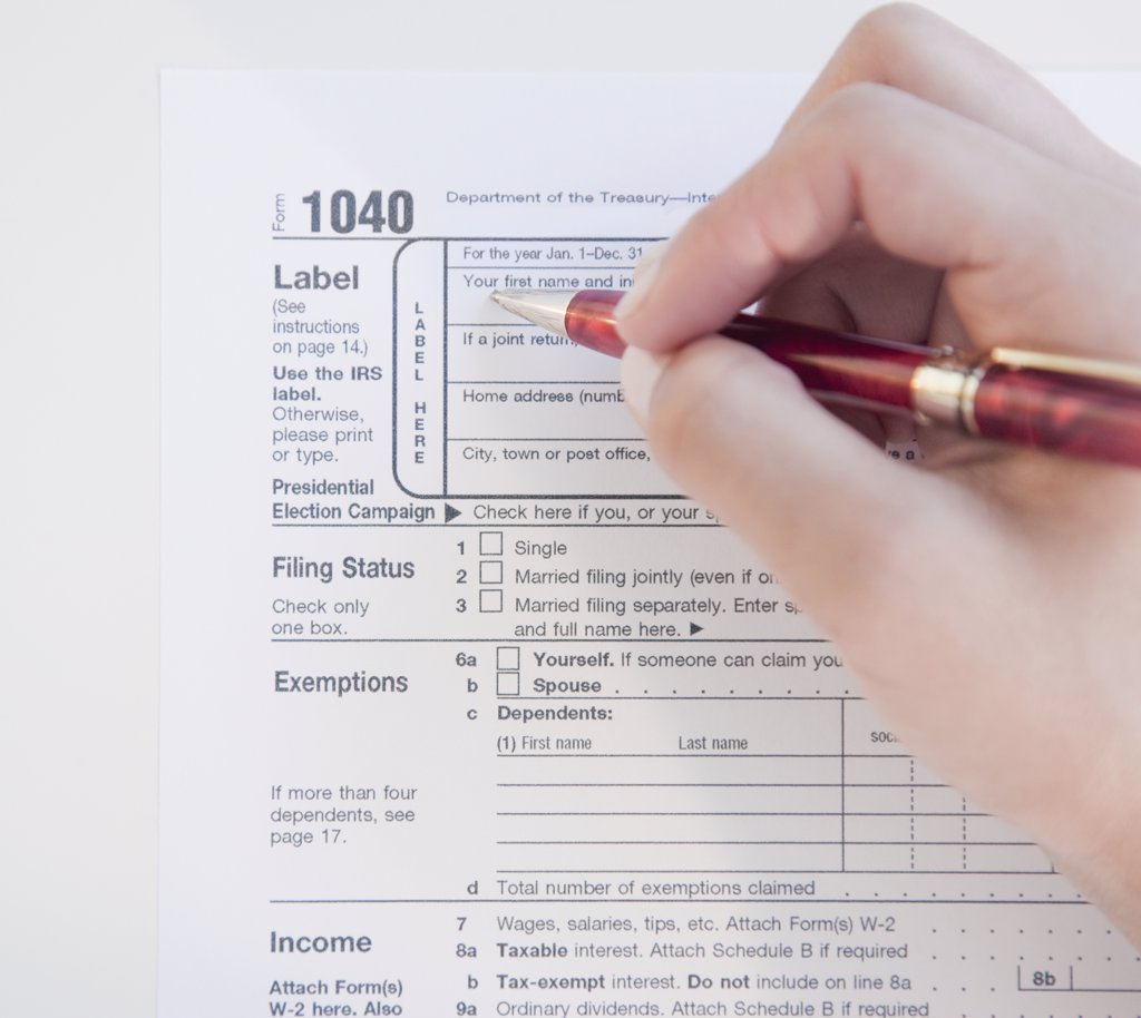 Stock Photo: 1589R-76650 Woman completing tax form