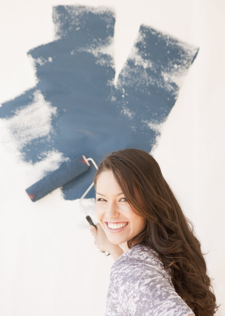 Mixed race woman painting wall : Stock Photo