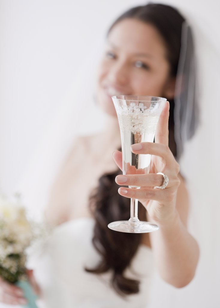 Mixed race bride holding champagne flute : Stock Photo