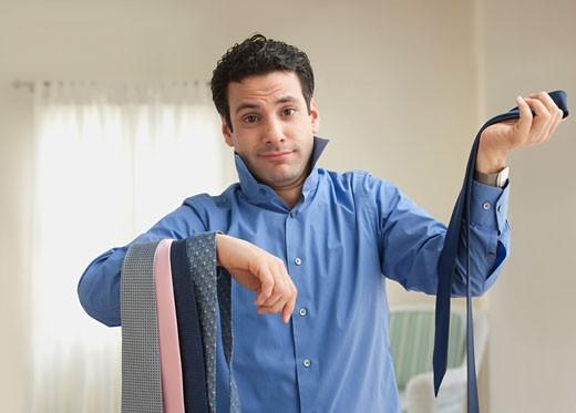 Stock Photo: 1589R-76744 Mixed race man choosing tie to wear