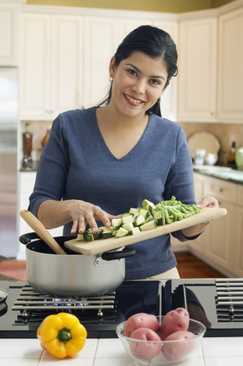 Stock Photo: 1589R-76764 Hispanic woman cooking vegetables
