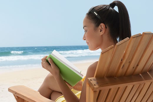Stock Photo: 1589R-76916 Mixed race woman reading on beach