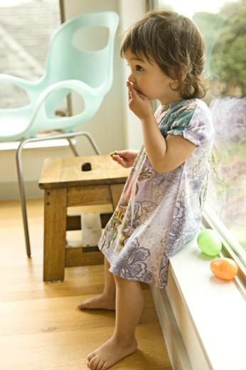 Stock Photo: 1589R-76976 Mixed race toddler sitting on window ledge
