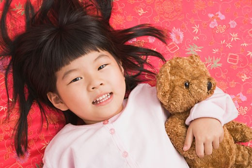Chinese girl laying with teddy bear : Stock Photo