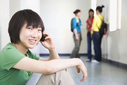 Stock Photo: 1589R-77011 Chinese woman talking on cell phone in corridor