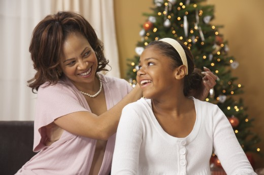 Mother fixing daughter's hair in front of Christmas tree : Stock Photo