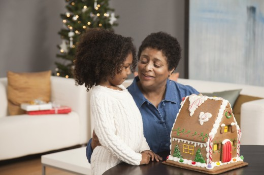Stock Photo: 1589R-77324 Grandmother and granddaughter looking at gingerbread house