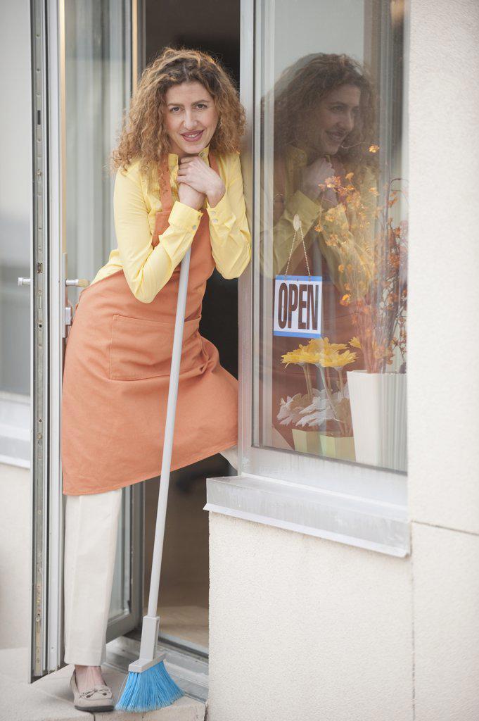 Stock Photo: 1589R-77429 Hispanic shopkeeper holding broom in doorway