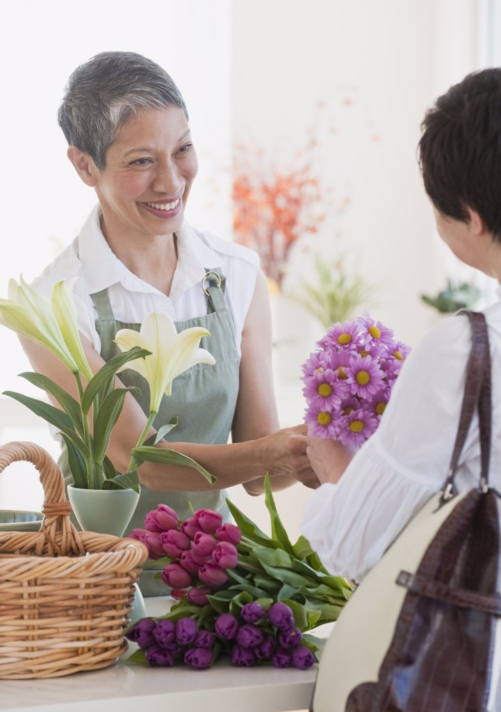 Chinese florist giving flowers to customer : Stock Photo