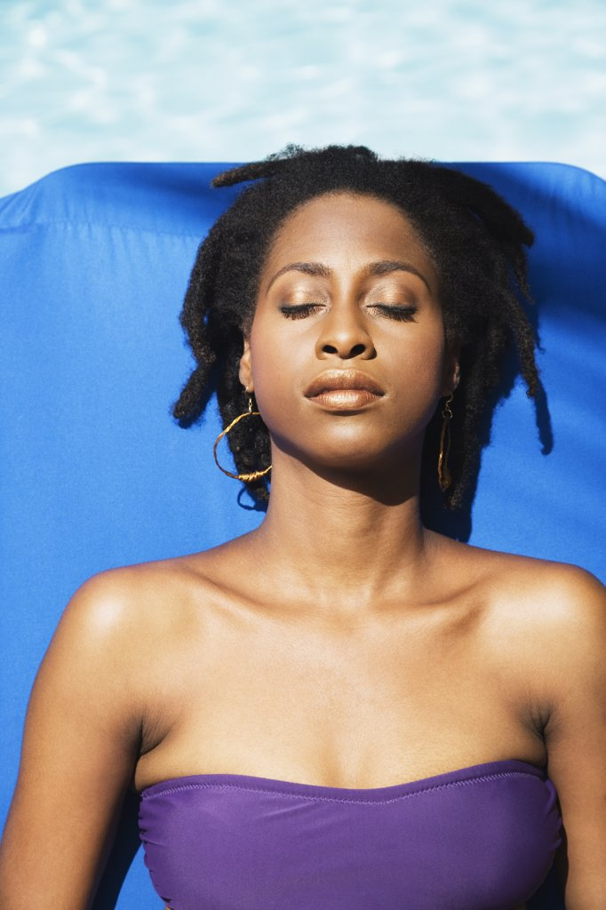 African woman sunbathing with eyes closed : Stock Photo