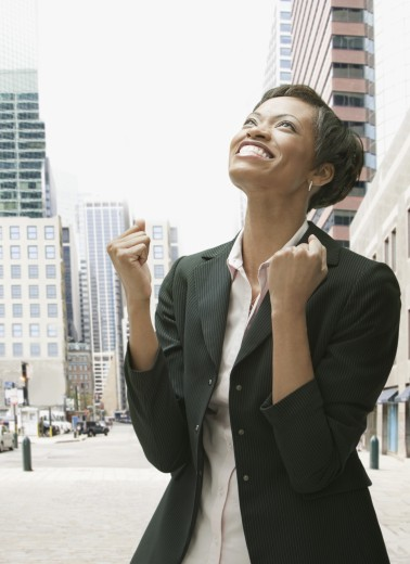 African businesswoman gesturing and smiling : Stock Photo