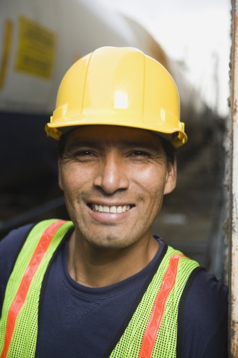 Smiling Hispanic man wearing hard hat and safety vest : Stock Photo