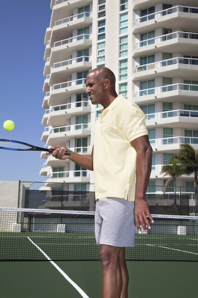 Stock Photo: 1589R-77871 African man balancing tennis ball on racket