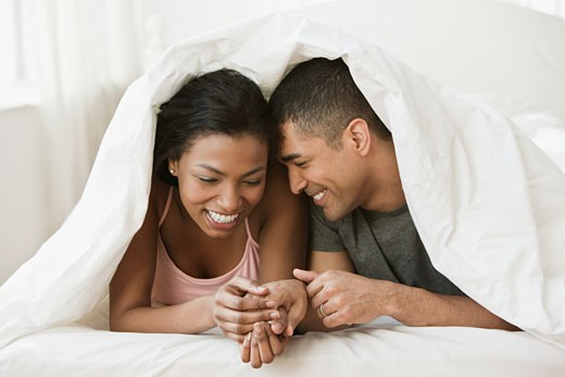 Stock Photo: 1589R-77957 Couple holding hands and laying under blanket in bed