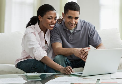 Stock Photo: 1589R-77968 Couple paying bills online in living room