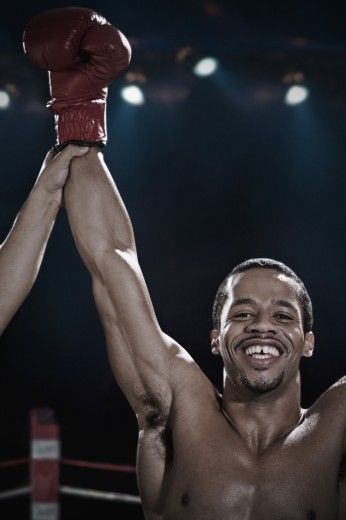 Stock Photo: 1589R-78065 Smiling mixed race boxer with arms raised in boxing ring